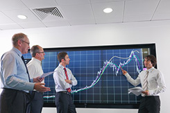 Business meeting with graphs on screen